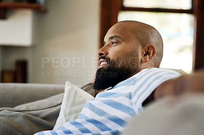 Buy stock photo Cropped shot of a handsome young man smiling while relaxing on a couch in his living room at home
