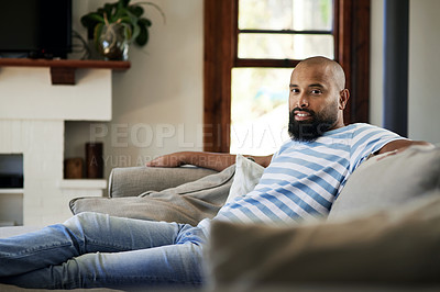 Buy stock photo Cropped portrait of a handsome young man smiling while relaxing on a couch in his living room at home