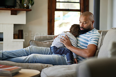 Buy stock photo Cropped shot of an affectionate young single father holding his sleeping little son in their living room at home
