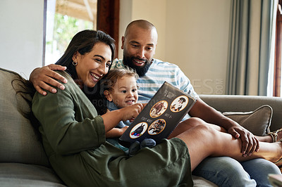 Buy stock photo Cropped shot of an affectionate young couple reading a picture book with their little son in their living room at home