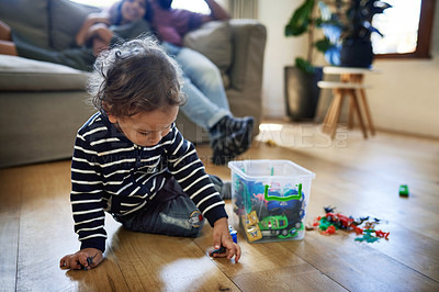 Buy stock photo Shot of an adorable little boy playing with his toy cars at home with his parents in the background