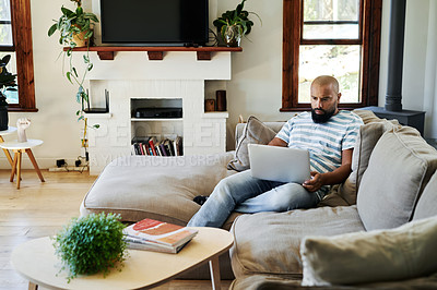 Buy stock photo Full length shot of a handsome young man using a laptop while relaxing in his living room at home
