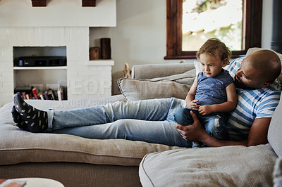 Buy stock photo Full length shot of an affectionate young single father spending time with his little son in their living room at home
