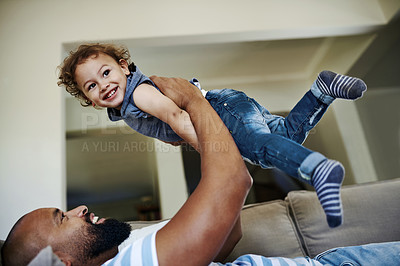 Buy stock photo Cropped shot of an affectionate young single father lifting his little son playfully in their living room at home