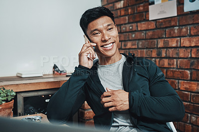 Buy stock photo Cropped shot of a handsome young male fitness instructor taking a phonecall while working in a gym
