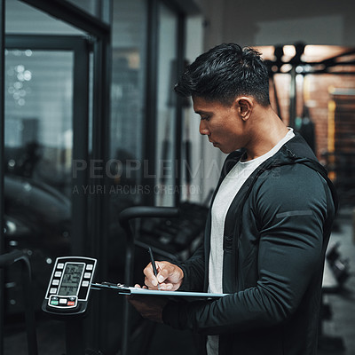 Buy stock photo Cropped shot of a handsome young male fitness instructor inspecting exercise equipment while working in a gym