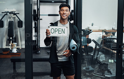 Buy stock photo Cropped portrait of a handsome young male fitness instructor holding up a sign that says