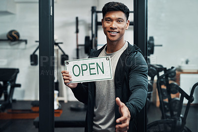 Buy stock photo Cropped portrait of a handsome young male fitness instructor extending his hand for a handshake while holding up a sign that says