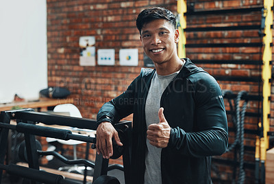 Buy stock photo Cropped portrait of a handsome young male fitness instructor showing thumbs up while standing in a gym