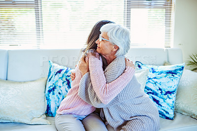 Buy stock photo Shot of a young woman hugging her mother on the sofa at home