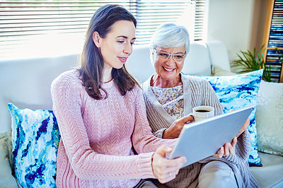 Buy stock photo Shot of a young woman using a digital tablet and having coffee with her mother at home