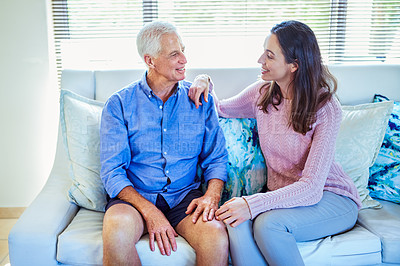Buy stock photo Shot of a young woman spending quality time with her father on the sofa at home