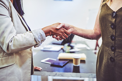 Buy stock photo Closeup shot of two unrecognisable businesswomen shaking hands in an office