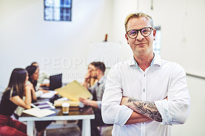 Buy stock photo Portrait of a young businessman standing in a office with his colleagues in the background