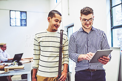 Buy stock photo Shot of two businessmen using a digital tablet in an office with their colleagues in the background