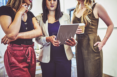 Buy stock photo Closeup shot of a group of businesswomen using a digital tablet together in an office