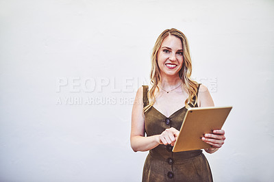 Buy stock photo Studio portrait of a young businesswoman using a digital tablet against a white background