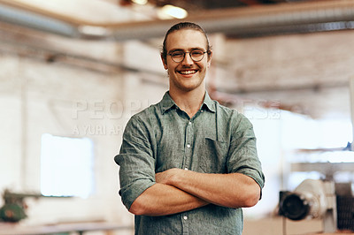 Buy stock photo Portrait of a young carpenter posing with his arms folded inside a workshop