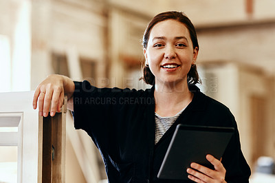 Buy stock photo Portrait of a young female carpenter using a digital tablet while working inside her workshop