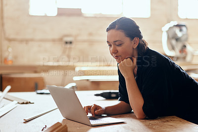Buy stock photo Cropped shot of a young female carpenter using a laptop while working inside her workshop
