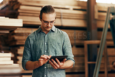 Buy stock photo Cropped shot of a young carpenter using a digital tablet while working inside his workshop