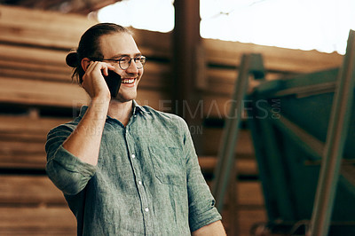 Buy stock photo Cropped shot of a young carpenter talking on a cellphone while working inside his workshop