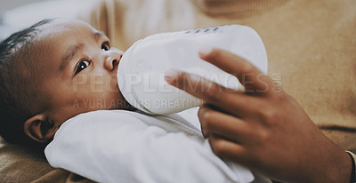 Buy stock photo Shot of an adorable baby boy being bottle fed milk at home by his father