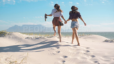 Buy stock photo Rearview shot of two young women holding hands and running on the beach