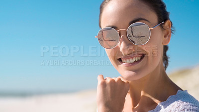 Buy stock photo Portrait of an attractive young woman wearing sunglasses and enjoying herself on the beach