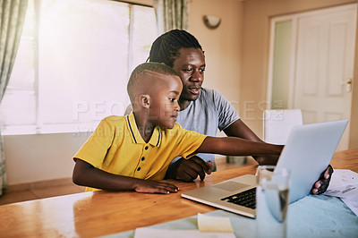 Buy stock photo Cropped shot of an adorable little boy using a laptop with his father at home