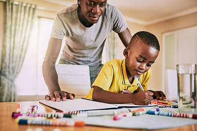 Buy stock photo Cropped shot of an adorable little boy doing his homework with his dad monitoring him in the background