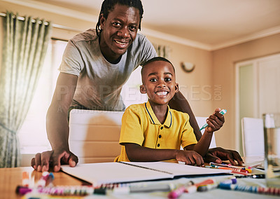 Buy stock photo Cropped portrait of an adorable little boy smiling while doing his homework with his father at home