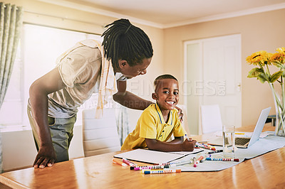 Buy stock photo Cropped shot of an adorable little boy smiling while doing his homework with his dad at home