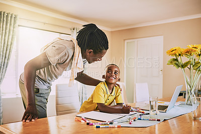 Buy stock photo Cropped shot of an adorable little boy smiling at his father while doing his homework at home