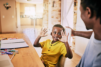 Buy stock photo Cropped shot of an adorable little boy showing his dad his answer while doing his homework at home