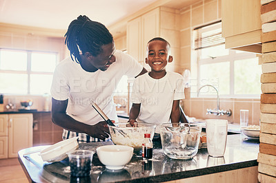 Buy stock photo Cropped portrait of a handsome young man standing and making a pancake batter with his adorable son in their home