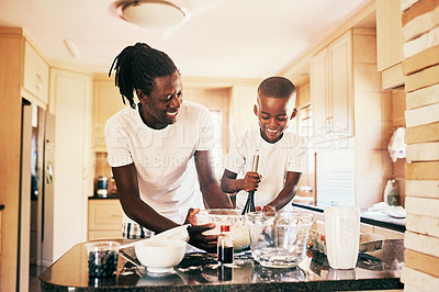 Buy stock photo Cropped shot of a handsome young man standing and making a pancake batter with his adorable son in their home