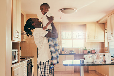 Buy stock photo Cropped shot of an adorable young boy bonding with his father during a weekend at home