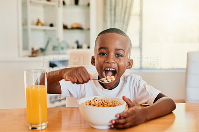 Buy stock photo Cropped portrait of a happy young boy eating his cereal for breakfast while sitting alone at the table