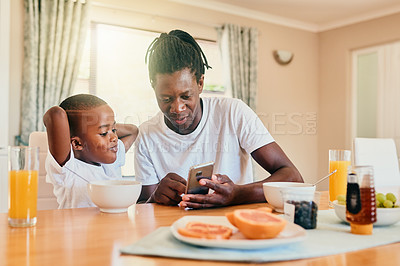 Buy stock photo Cropped shot of a happy father and son bonding over breakfast and technology during a weekend at home