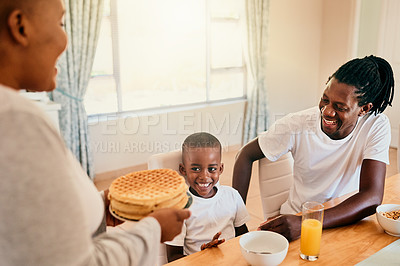Buy stock photo Cropped shot of an attractive young woman holding a plate of waffles for breakfast with her family at home