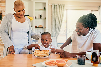 Buy stock photo Cropped shot of a happy young family enjoying waffles and bonding over breakfast in their home