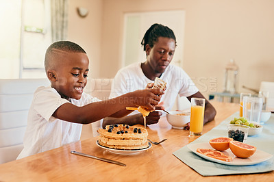 Buy stock photo Cropped shot of an adorable young boy pouring honey over his waffles while having breakfast with his father at home