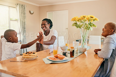Buy stock photo Cropped shot of a handsome young man sitting and giving his son a high five during breakfast at home