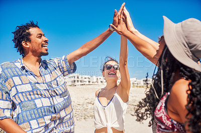 Buy stock photo Shot of a group of friends giving each other a high five on the beach