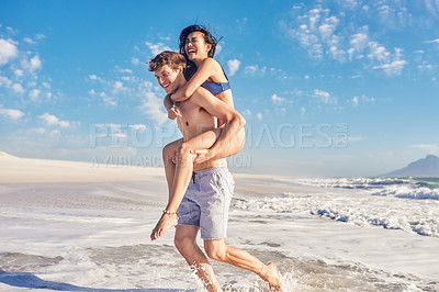 Buy stock photo Shot of a young man giving his girlfriend a piggyback ride on the beach
