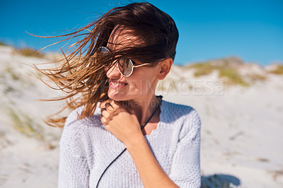 Buy stock photo Shot of an attractive young woman wearing sunglasses and enjoying herself at the beach