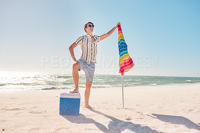 Buy stock photo Full length shot of a handsome young man posing with his cooler box and beach umbrella at the beach