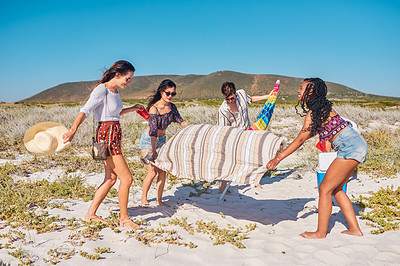 Buy stock photo Full length shot of a group of young friends setting up to have a picnic together at the beach