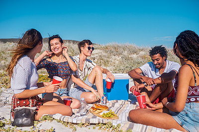 Buy stock photo Shot of a group of young friends having a picnic together at the beach